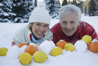 Couple with lemons and oranges in snow