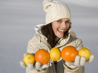 Woman holding lemons and oranges in winter
