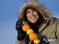 Man holding lemons and oranges in winter