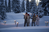 Couples holding torches at night in winter