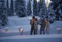 Couples holding torches at night in winter 20025272062| 写真素材・ストックフォト・画像・イラスト素材|アマナイメージズ