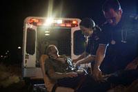 Paramedics with Injured Man by Ambulance