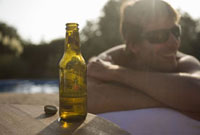 Man Relaxing by Swimming Pool With a Bottle of Beer