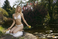 Young woman sitting by pond, holding water lily