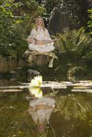 Young woman meditating, outdoors 20025287760  写真素材・ストックフォト・画像・イラスト素材 アマナイメージズ