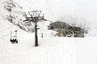 Switzerland, Graubunden, Arosa, Skiers riding chairlift
