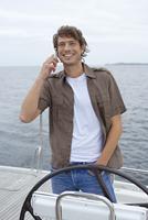 Germany, Baltic Sea, Lubecker Bucht, Young man on yacht using mobile phone 20025288028  写真素材・ストックフォト・画像・イラスト素材 アマナイメージズ
