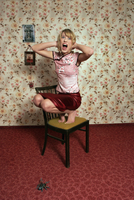 Young woman cowering on chair, spider on floor