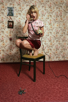 Woman cowering on chair, phoning, spider on floor