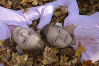 Two girls laying on autumn leafs, portrait