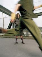 Woman standing on bridge, man running 20025288299| 写真素材・ストックフォト・画像・イラスト素材|アマナイメージズ