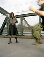 Woman standing on bridge, man running