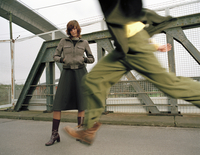 Woman standing on bridge, man running 20025288301| 写真素材・ストックフォト・画像・イラスト素材|アマナイメージズ