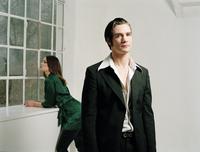 Man in pinstripe suit, portrait, woman looking out of window