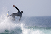 Spain, Canary Islands, Fuerteventura, Surfer riding a breaking wave