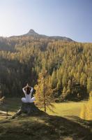 Woman meditating on a tree trunk