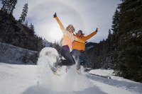 Austria, Salzburger Land, Young couple jumping in snow