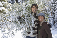 Austria, Salzburger Land, Altenmarkt, Young couple in snowscape carrying fir tree 20025288848| 写真素材・ストックフォト・画像・イラスト素材|アマナイメージズ