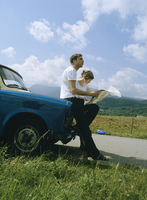 Couple with map, leaning on car