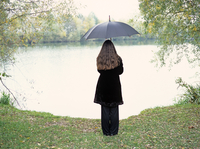 Young woman with umbrella standing at a lake 20025290135| 写真素材・ストックフォト・画像・イラスト素材|アマナイメージズ