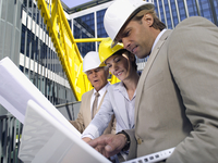 Germany, Baden Wurttemberg, Stuttgart, Men and woman in hard hats looking at blueprints