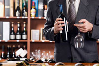 Businessman holding a wine glass and a wine bottle