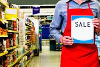 Sales clerk holding a sale signboard