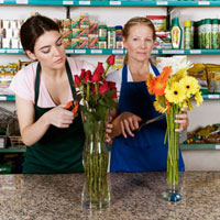 Two female florists arranging flowers in vases