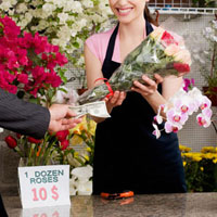 Customer giving cash payment to a female florist