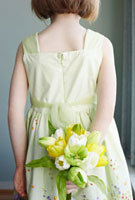 Girl Wearing Easter Dress Holding Flowers Behind Her Back