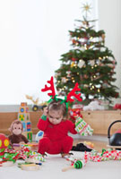 Littel Girl Unwrapping Toys next to Christmas Tree