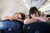 Two Little Girls Looking Over Seats on Airplane