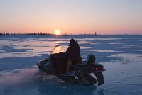 Man Riding Snowmobile at Sunset, Churchill, Manitoba, Canada