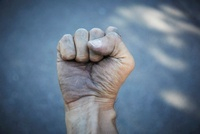 Man's Dirty Hand Clenched into Fist