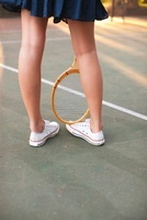 Legs of Young Woman and Tennis Racquet