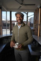 Afro-American barista man holding espresso in coffee barProp