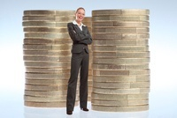 Businesswoman Standing in front of Stacks of Large Coins