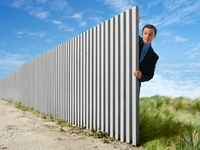 Businessman Peeking Out from Behind Eternal Fence