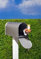 Hand Holding Pill Bottle Sticking Out of Mailbox