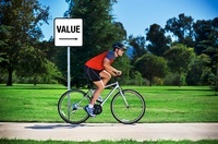 Man Riding Bicycle Past Sign Pointing to Value