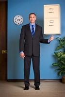 Businessman Balancing Filing Cabinet onFingertip