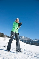 Woman Walking with Ski Poles Outdoors in Winter