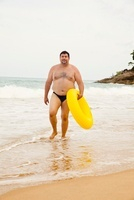 Man on Beach with Inflatable Ring