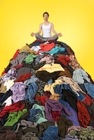 Woman Meditating on Pile of Clothing