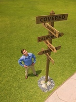 Man Looking Up at Directional Signs