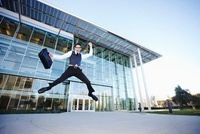 Businessman Leaping in front of Building