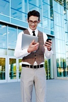 Businessman Holding Cell Phone and Tablet PC