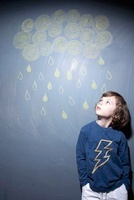 Boy Looking at Chalk Drawing of Clouds and Rain