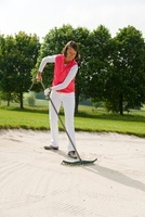 Woman Raking Sandpit on Golf Course