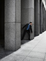Businessman Peeking Around Column